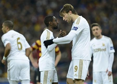Swansea City's Nathan Dyer is consoled by Miguel Michu after he wasn't allowed to take a penalty during their English League Cup final soccer match against Bradford City at Wembley Stadium in London