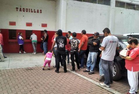 Aficionados del Irapuato recogiendo el dinero de sus entradas.